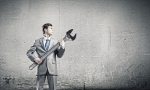 Young businessman with wrench against cement background